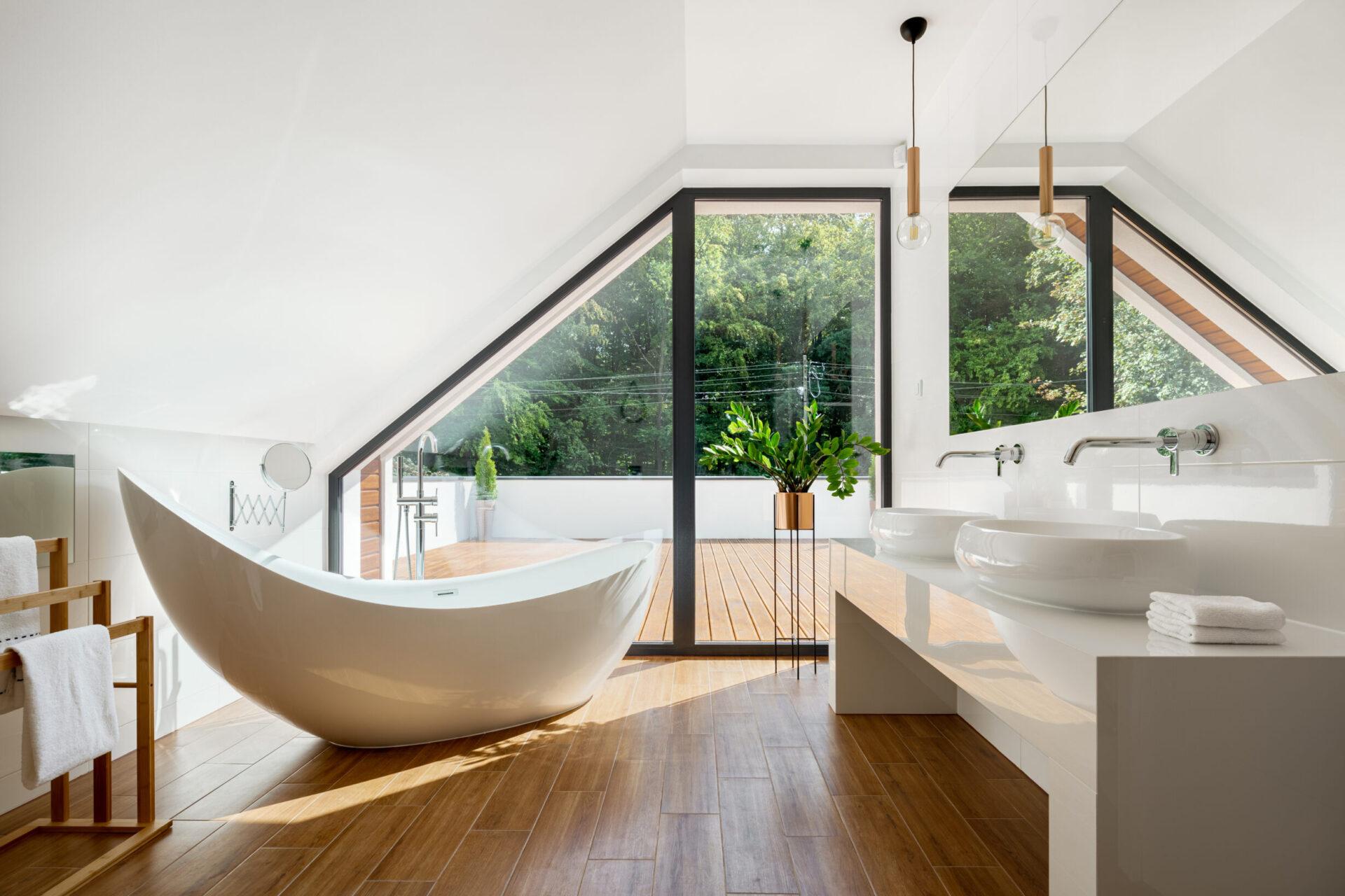 Elegant attic bathroom with stylish bathtub, wooden floor and balcony door